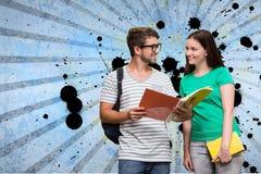 Estudantes novos felizes que mantêm cadernos contra o fundo chapinhado azul Imagens de Stock
