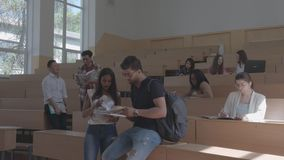 Estudantes novos que comunicam-se na sala de aula