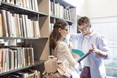 Estudantes novos que discutem sobre o livro ao estar pela prateleira na biblioteca imagens de stock