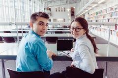 Estudantes novos que estudam com o PC da tabuleta na biblioteca Fotos de Stock