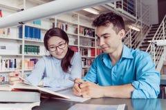 Estudantes novos que estudam na biblioteca Fotos de Stock Royalty Free