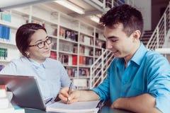 Estudantes novos que estudam na biblioteca Foto de Stock