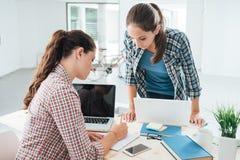 Estudantes novos que fazem seus trabalhos de casa Imagens de Stock Royalty Free