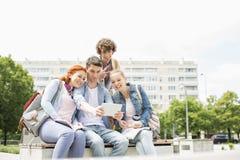 Estudantes novos que fotografam-se através da tabuleta digital no terreno da faculdade fotografia de stock