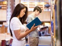 Estudantes novos que lêem um livro ao estar acima Foto de Stock Royalty Free