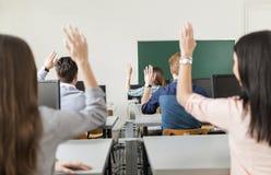 Estudantes novos que levantam as mãos em uma sala de aula Fotografia de Stock