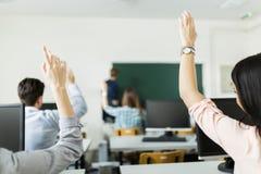 Estudantes novos que levantam as mãos em uma sala de aula Imagens de Stock Royalty Free