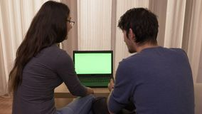 Estudantes novos que sentam-se no sofá em casa que discute e que compara preços do Internet usando um portátil com a tela verde filme
