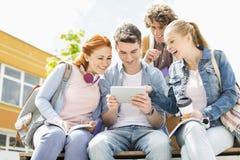 Estudantes novos que usam a tabuleta digital no terreno da faculdade foto de stock