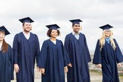Estudantes ou licenciado felizes em placas do almofariz imagens de stock royalty free