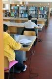 Estudantes para trás em uma biblioteca da universidade imagens de stock