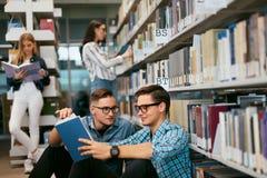 Estudantes que aprendem o livro de leitura na biblioteca da universidade fotografia de stock