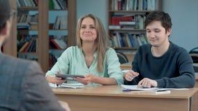 Estudantes que datilografam no tablet pc em uma sala de aula Fotografia de Stock