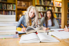 Estudantes que escrevem notas com a pilha de livros na mesa da biblioteca Imagem de Stock