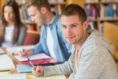 Estudantes que escrevem notas na mesa da biblioteca fotografia de stock