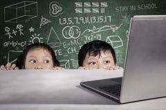 Estudantes que espreitam o portátil com garrancho no quadro Fotografia de Stock Royalty Free