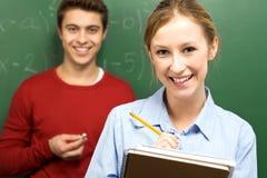 Estudantes que estão ao lado do quadro-negro Foto de Stock Royalty Free