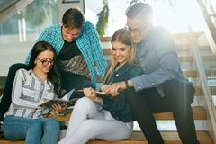 Estudantes que estudam, lendo a informação educacional na faculdade fotos de stock royalty free