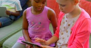 Estudantes que estudam na tabuleta digital na biblioteca escolar 4k video estoque