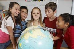 Estudantes que examinam o globo imagens de stock