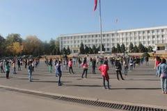 Estudantes que exercitam na frente da câmara municipal de Osh imagens de stock