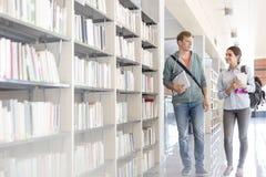 Estudantes que falam ao andar pela estante na biblioteca da universidade fotografia de stock