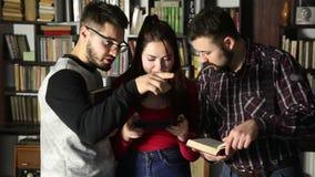 Estudantes que falam junto na biblioteca e que procuram pela informação Comparando a tabuleta com o livro video estoque