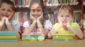 Estudantes que inclinam-se em uma tabela e que olham a câmera com os livros na frente deles em uma biblioteca video estoque