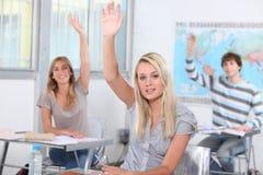Estudantes que levantam as mãos Fotografia de Stock