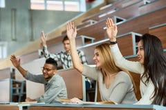 Estudantes que levantam as mãos na classe imagens de stock