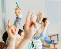 Estudantes que levantam as mãos na classe