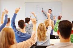 Estudantes que levantam as mãos na faculdade fotos de stock royalty free
