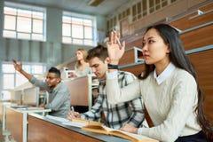 Estudantes que levantam as mãos na faculdade imagem de stock