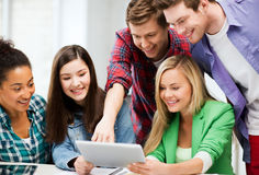Estudantes que olham o PC da tabuleta na leitura na escola Foto de Stock