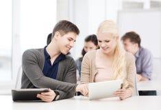 Estudantes que olham o PC da tabuleta na leitura na escola Imagens de Stock