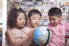 Estudantes que olham um globo Fotos de Stock Royalty Free