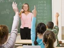 Estudantes que respondem à pergunta do professor Imagens de Stock