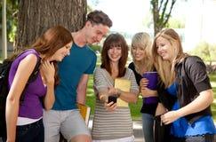 Estudantes que riem do telefone Fotos de Stock Royalty Free