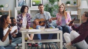 Estudantes que têm o divertimento que joga a guitarra, cantando e bebendo no partido em casa filme