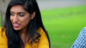Estudantes que têm uma conversação junto no gramado vídeos de arquivo