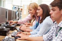 Estudantes que trabalham em computadores na biblioteca com professor Fotografia de Stock Royalty Free