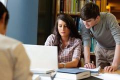 Estudantes que trabalham junto com um portátil Imagem de Stock
