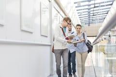 Estudantes que trocam livros ao andar no corredor na faculdade imagens de stock