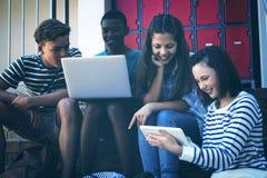 Estudantes que usam o portátil, o telefone celular e a tabuleta digital na escadaria imagem de stock