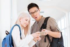 Estudantes que usam o smartphone no salão da universidade imagens de stock royalty free