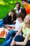 Estudantes que usam o tablet pc ao fazer trabalhos de casa no parque Imagens de Stock