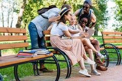 Estudantes que usam a tabuleta ao descansar no banco no parque foto de stock royalty free