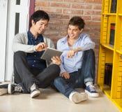 Estudantes que usam a tabuleta de Digitas ao sentar-se perto Fotografia de Stock Royalty Free