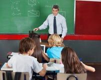 Estudantes que usam a tabuleta e a calculadora Fotos de Stock Royalty Free