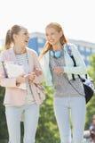 Estudantes universitário fêmeas novas alegres que andam no terreno Foto de Stock Royalty Free